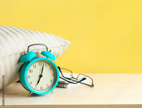 Morning turquoise Alarm clock near the pillow on the bedside table on yellow wal Wallpaper Mural