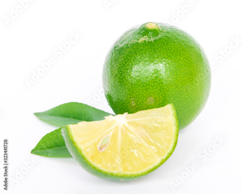 Photo Studio shot single whole lime with slice cutout and leaves isolated on white