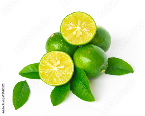 Pile of homegrown Asian limes with half cuts slices and green leaves isolated on Wallpaper Mural