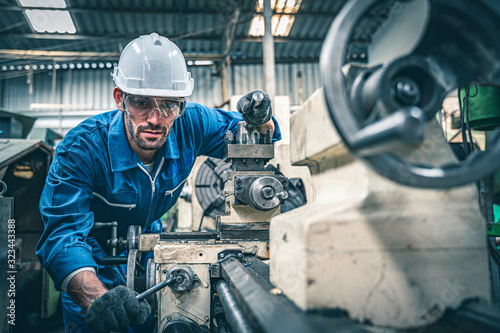Foto Male worker in blue jumpsuit and white hardhat operating lathe machine