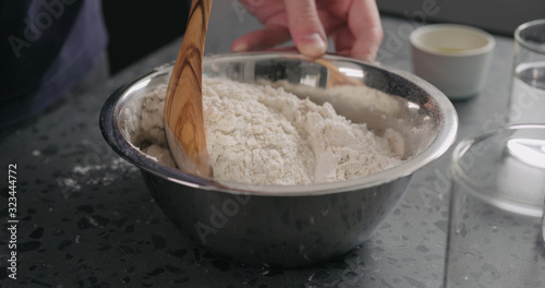 Obraz na plátně man mixing dry ingredients with flour in steel bowl on concrete countertop