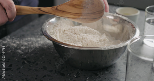 man mixing dry ingredients with flour in steel bowl on concrete countertop