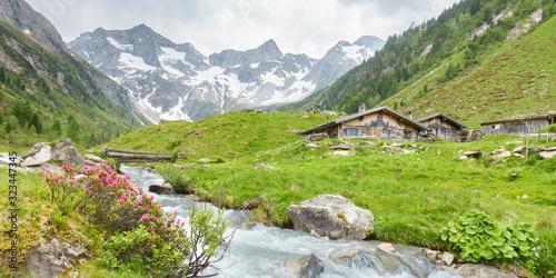 Vászonkép Panorama von Almhütten mit Gebirgsfluß im Zillertal und Gletscher im Hintergrund
