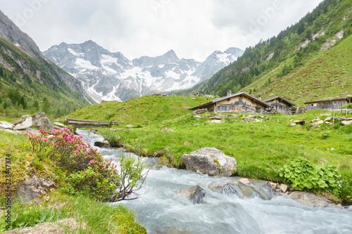 Almhütten mit Gebirgsfluß im Zillertal und Gletscher im Hintergrund Canvas-taulu
