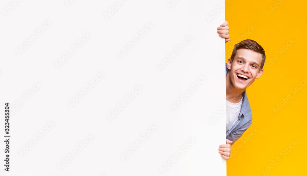 Fototapeta Emotional young guy peeking out from advertising empty board