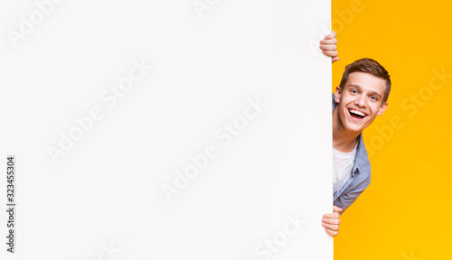 Fotografía Emotional young guy peeking out from advertising empty board