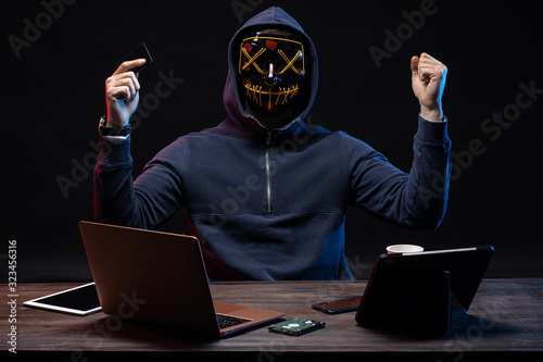 Fototapety, obrazy: anonymous hacker in mask after successful getting access to bank card, raised hands up, hold bank card in one hand, going to withdraw money from it. isolated over black background