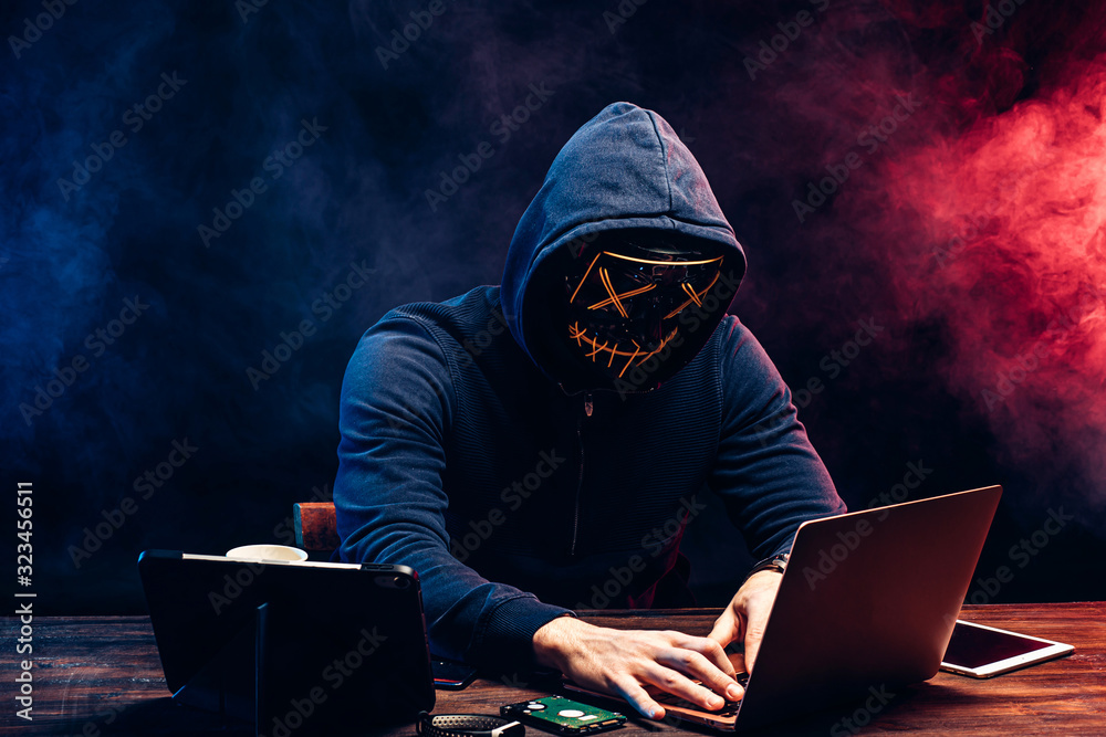 Fototapeta young criminal male hides his face under the hood and mask, hacks the password on the laptop, typing something. anonymous, incognito guy going to hack. cyberattack concept