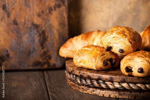 Freshly baked sweet buns puff pastry with chocolate and croissants on old wooden background Canvas Print