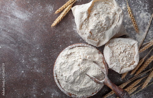 Wooden bowl of wheat flour on kitchen background top view Fototapete