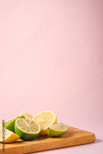 Fresh tasty lemon and lime citrus fruits slices on wooden cutting board, minimal pink background isolated, angle view