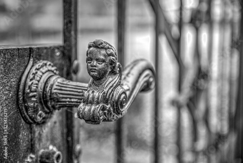 old metal gate handle with the face of a child on the top