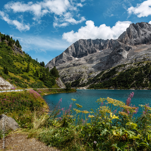 Wall mural - Wonderful Summer landscape. Fedaia lake with Marmolada peaks covered by ice, Dolomites, Italy. Amazing nature landscape. Picture of wild area