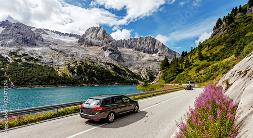 Wall mural - Scenic drive near Fedaia lake and Marmolada mountain with colorful sky during sunset. Gran Poz location, Trentino-Alto Adige. Italy, Amazing nature Landscape