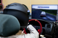 A Professional Racer In A Black Helmet And A White Homologated Suit Sits In The Sports Seat Of A Car For Drifting And Racing During A Race And Training On A Simulator.