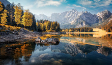 Awesome Sunny Landscape In The Forest. Wonderful Autumn Scenery. Picturesque View Of Nature Wild Lake. Sun Rays Through Colorful Trees. Incredible View On Fusine Lakeside. Amazing Natural Background
