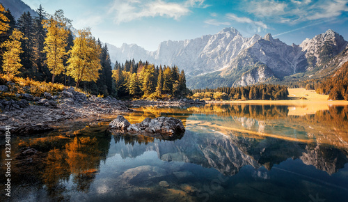 Fototapeta jesień   awesome-sunny-landscape-in-the-forest-wonderful-autumn-scenery-picturesque-view-of-nature-wild-lake-sun-rays-through-colorful-trees-incredible-view-on-fusine-lakeside-amazing-natural-background