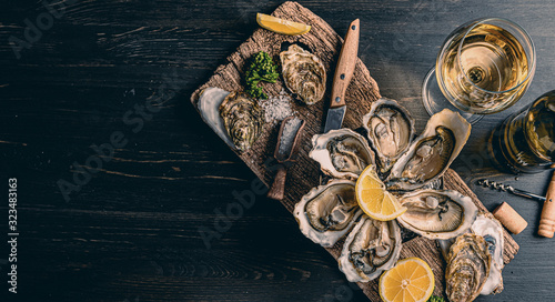 Photo Fresh oysters with lemon ice and white wine.