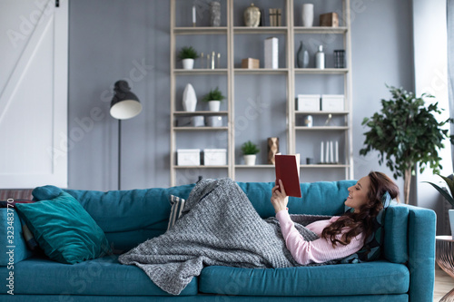 Fototapeta Happy woman with a book in her hands resting on a cozy sofa at home. obraz