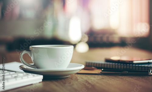 Photo Closeup white cup of coffee with smartphone, notebook  on wooden table in cafe