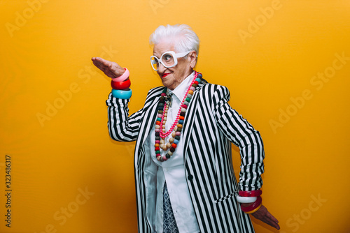 Fototapeta Funny grandmother portraits. Senior old woman dressing elegant for a special event. granny fashion model on colored backgrounds obraz