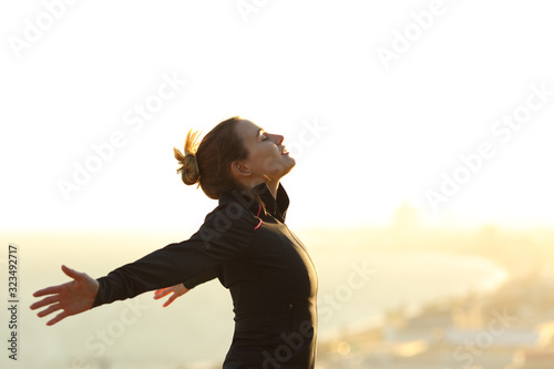 Fotografiet Runner relaxing breathing fresh air outstretching arms