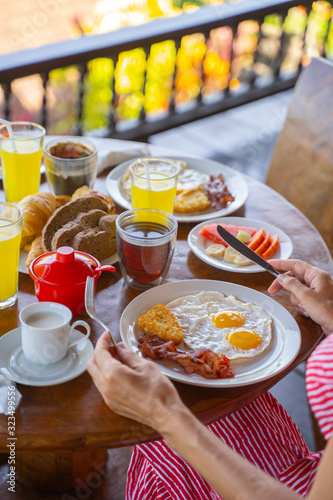 Young lady eating fried eggs with bacon in outdoor cafe