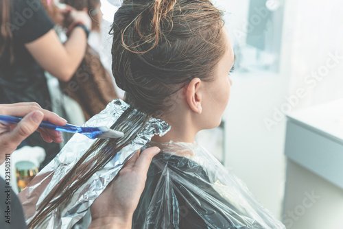 Fototapeta Hairdresser coloring young woman hair using foil