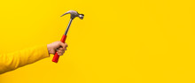 Female Hand Holding Hammer On Yellow Background, Panoramic Mock-up