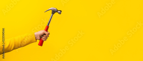 Fotografie, Obraz Female hand holding hammer on yellow background, panoramic mock-up