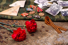 Victory Day. Carnations On A Background Of Rusty Iron With Old Military Letters, Photographs, St. George Ribbon And Medals. The Great Patriotic War.