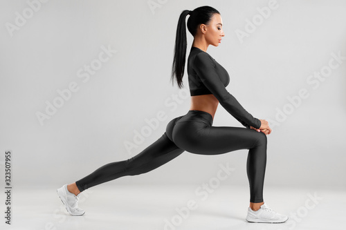 Fototapeta Fitness woman doing lunges exercises for leg muscle workout training. Active girl doing front forward one leg step lunge exercise for butt, isolated obraz