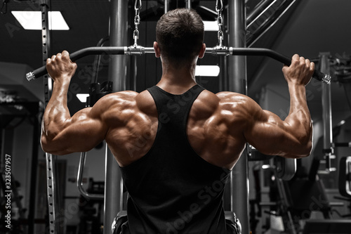 Muscular man workout in gym, doing exercise for back lat pulldown. Strong mal...