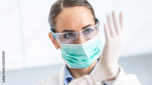 Fotografía Doctor woman surgeon specialist in sterile clothing putting on surgical gloves
