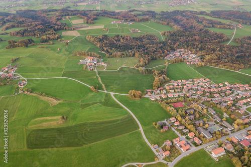 Valokuvatapetti Aerial view of small town with red tiled roofs among green farm fields and distant forest in summer