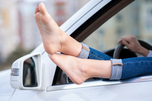 Close Up Of Woman Driver Bare Feet Sticking Out Of A Car Open Window.