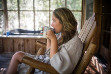 Young Attractive Woman In Robe Sipping Morning Coffee On A Rustic Porch Enjoying Mother's Day Self Care