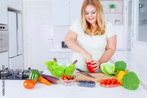 Blonde overweight woman preparing fresh vegetable