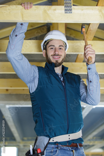 male builder on the roof of a wooden frame house Tableau sur Toile