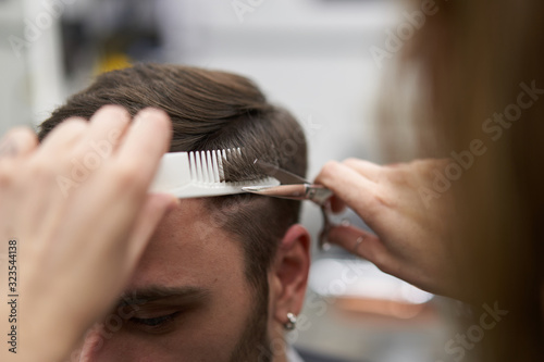 Beautiful caucasian woman hairdresser doing hairstyle to client.