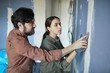 Waist up portrait of young couple smoothing dry wall while renovating house together, copy space