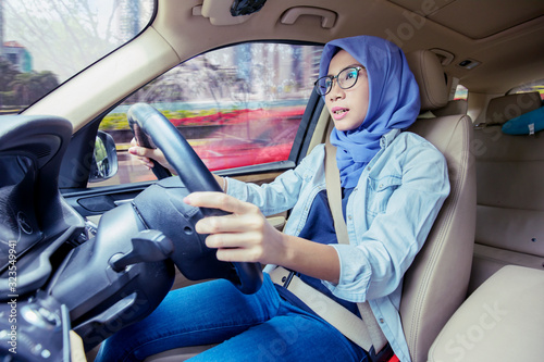 Portrait of young muslim woman driving car