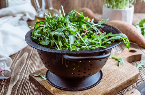 Photo Fresh organic arugula leaves in black colander