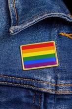 Gay Pride Flag Pin On A Denim Jacket For LGBTQ Identity, Pride, And Activism. The Flag Design Is Public Domain For All Uses.