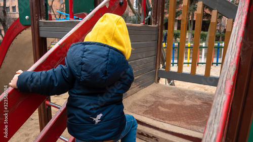 A toddler enjoys outdoors in winter on a sunny day in a public park in Madrid Wallpaper Mural