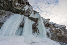 Large Icicles Hanging Off A High Jagged Mountain With Blue Sky And Clouds In The Background. The Wall Of Ice Has A Blue Tint And Heavy Texture. The Waterfall Of Ice Spans Down To A Mound Of Snow.
