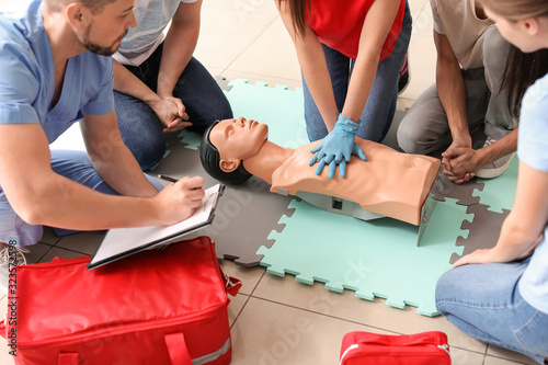 Photo Instructor demonstrating CPR on mannequin at first aid training course
