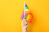 Fototapeta Rainbow - Female hand with rainbow flag on color background. LGBT concept