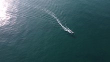 Scenic Aerial View Of Fast Speedboat Leaving Long Wake, Tilt Down