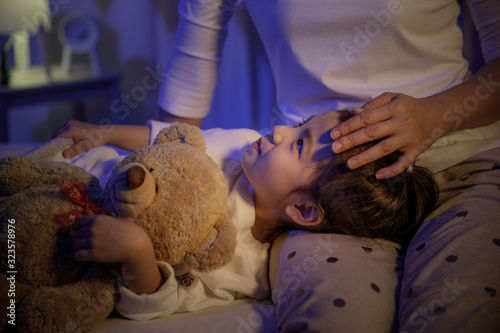 Photo Mother stroking head of cute girl then sleeping on mom lap on bed in a dark bedr